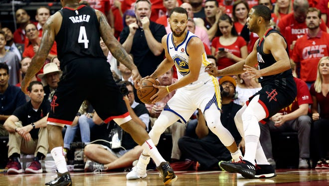 Golden State Warriors guard Stephen Curry (30) dribbles the ball in between Houston Rockets forward PJ Tucker (4) and guard Eric Gordon (10) during the first quarter in game seven of the Western conference finals of the 2018 NBA Playoffs at Toyota Center.