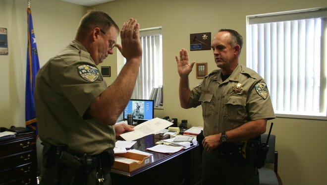 Lyon County Sheriff Al McNeil administers the oath of office to new jail detention facility commander Frank Hunewill on Sept. 30.