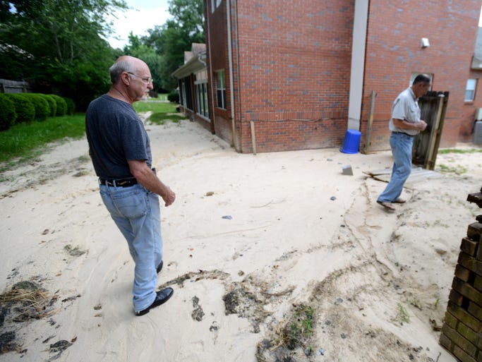 Ron Bansemer,left, and Richard Thayer walk down a muddy path caused by a damaged retention pond wall after the April 29 floodl. Residents in Woodbridge subdivision are frustrated with the muddy water each time it rains.