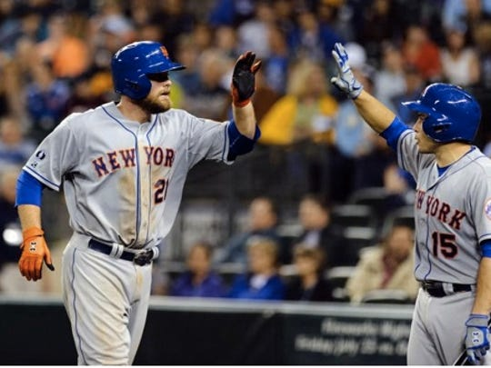 New York Mets first baseman Lucas Duda (21) and catcher Travis d'Arnaud (15) celebrate after Duda hit a solo home run against the Seattle Mariners during the eighth inning at Safeco Field Tuesday, July 22, 2014, in Seattle. (Steven Bisig-USA TODAY Sports)