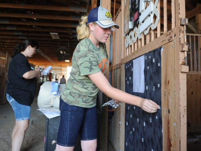 Paige Mox, 14, and her mother Deanna Mox decorate PaigeâjQuery1720026973549043759704_1407613791643s stall for her horse Eclipse the Midnight Star at the Muskingum County Fairgrounds. Paige is a member of Grand Entry 4-H Club. Groups came in Thursday to decorate the barn in preparation for the Muskingum County Fair.