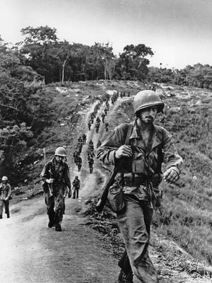 U.S. soldiers, bearded and weary, plod along a road toward an American base of operations in Guadalcanal, Solomon Islands in February 1943.