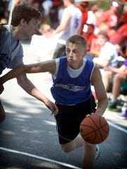 Logan Horn pushes past a Lancaster catholic player to reach the basket. Cedar Crest athletes faced off against a Lancaster Catholic team for the championship game at Saturday's Sweep the Streets High School Basketball Tournament in Lebanon, June 25, 2016.