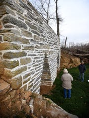 Jesse Copenhaver (back to camera) talks to his son, Ron, about the challenges of restoring this centuries-old lime kiln on Ron's farm off Route 72 in North Cornwall Township.