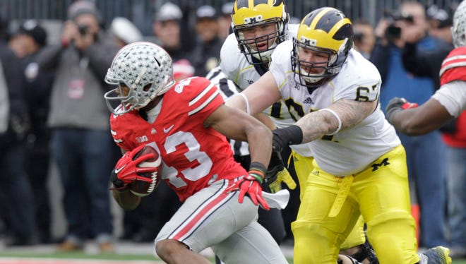 Ohio State linebacker Darron Lee, left, picks up a fumble in front of Michigan linemen Ben Braden, center, and Kyle Kalis and returns it for a touchdown Nov. 29, 2014, in Columbus, Ohio.