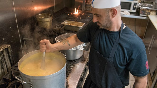 Mike Sobh stirs a large pot of simmering yellow lentil soup.