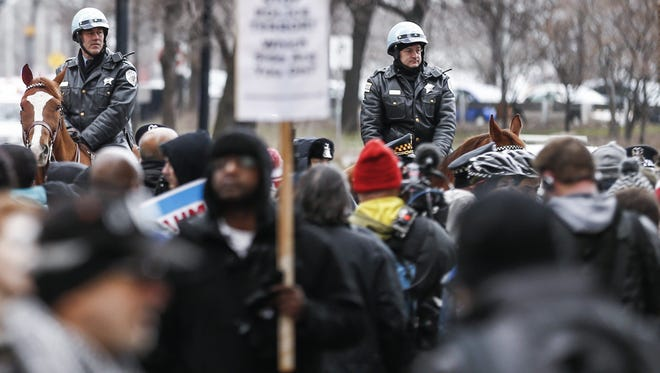 Mounted police officer block protestors as they march, chant, shout and block intersections and stores along Michigan Avenue's Magnificent Mile' shopping area as they call for the resignation of Chicago Mayor Rahm Emanuel in Chicago, Illinois, USA, 24 December 2015. Activists called for the demonstration on Christmas Eve as they continue to display dissatisfaction over the handling of the investigation into the police shooting of teenager Laquan McDonald.  EPA/TANNEN MAURY