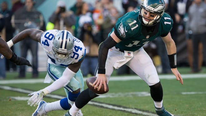 Philadelphia Eagles quarterback Carson Wentz (11) eludes the rush of Dallas Cowboys defensive end Randy Gregory (94) during the third quarter at Lincoln Financial Field.