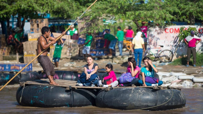 Migrants who appeared to be using coyotes on June 21, 2014, illegally cross into Mexico from Guatemala using a raft on the Suchiate River.