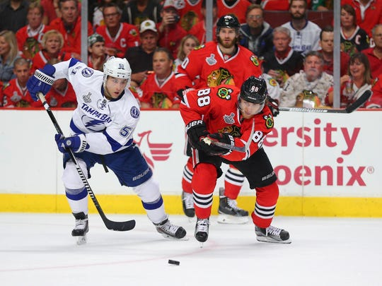 Blackhawks right wing Patrick Kane (88) chases the puck with Lightning center Valtteri Filppula (51) in the third period of Game 4 of the Stanley Cup Final at United Center.