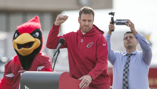 Cardinals Carson Palmer pumps his fist to the crowd during the pep rally/send off before heading to North Carolina for the NFC Championship at Phoenix Sky Harbor in Phoenix, AZ on January 23, 2016.