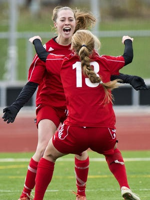 CVU's Emma Davitt, rear, and Kate Raszka celebrate the Redhawks' victory over Essex in the Division I state championship game.