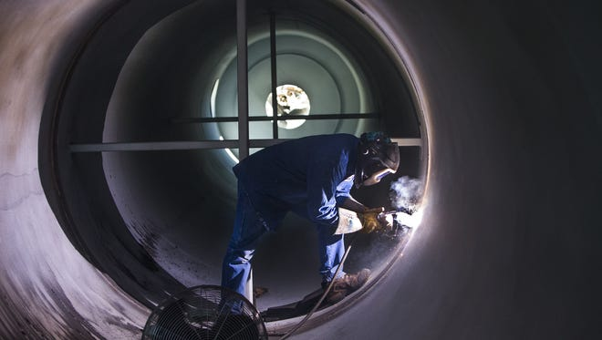 SRP metal fabricator Ivan Tsinnijinnie welds a replacement surge tank at the Kyrene Generating Station in Tempe on Sept. 21, 2017.