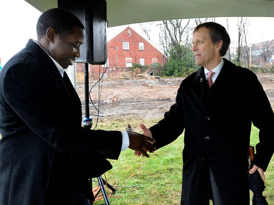 Principal owner of Titus Young Real Estate, D.J. Wootson, left, and John Ingram, chairman of Ingram Industries, shake hands after the 1821 Jefferson Street building ground-breaking ceremony on Jan 15, 2016.
