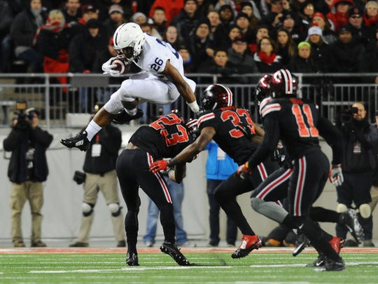 Penn State running back Saquon Barkley hurdles over Ohio State safety Tyvis Powell.