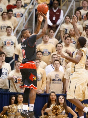 Louisville's Terry Rozier, left, hits a 3-pointer over Pittsburgh's Josh Newkirk, right, in the first half of an NCAA college basketball game Sunday, Jan. 25, 2015, in Pittsburgh. (AP Photo/Keith Srakocic)