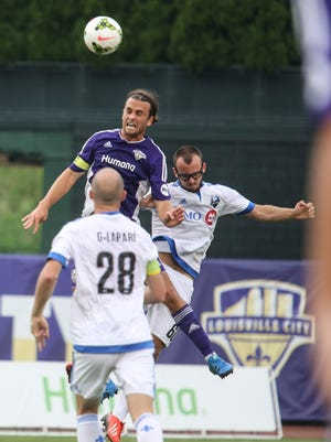 Louisville City forward Matt Fondy goes up for a header against Montreal's Mitchel Bringolf Wednesday night. Aug. 5, 2015