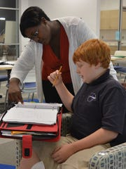 Sussex Academy's Discover Your Potential coordinator Brandis Thompson works with sixth-grader Joseph Minton after school Thursday, Nov. 5.
