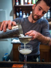 Justin Barrows makes a Gryphon Smokey Sour at The Gryphon in Burlington on Tuesday, January 26, 2016. The cocktail is made with Vida mezcal, muddled ginger and basil, sugar and an egg white.