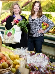 "Les Dames d'Escoffier group members Sherry Hurley, owner at Farm to Fork, and Lisa Windhorst in the Rainbow Blossom produce section. The group offers an outlet for women with passions in food to get involved and make a difference, such as with the Green Table Initiative, which will feature cooking demonstrations with local chefs using local produce. ""Local produce is becoming more accessible,"" Hurley said. ""But if people don't know how to cook it, they're not going to buy it.""  March 24, 2016"