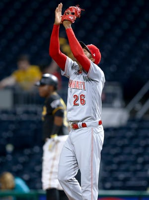 Cincinnati Reds relief pitcher Raisel Iglesias (26) celebrates after getting Pittsburgh Pirates' Gregory Polanco, rear, to ground out for the last out of a baseball game, Tuesday, April 11, 2017, in Pittsburgh. The Reds won 6-2. (AP Photo/Keith Srakocic)