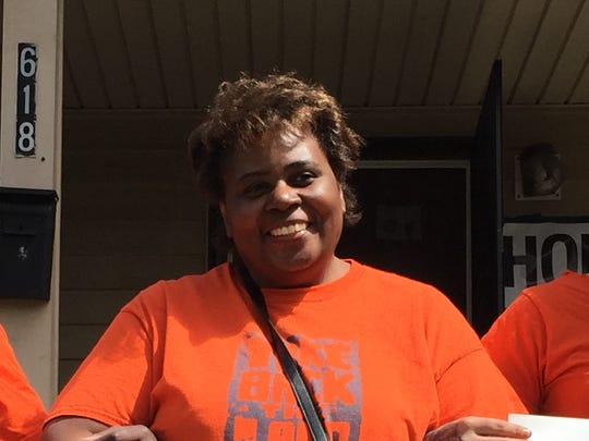 Elizabeth McGriff of Rochester stands with supporters outside the Cedarwood Terrace home she was evicted from in April, 2016. McGriff moved back in in May.