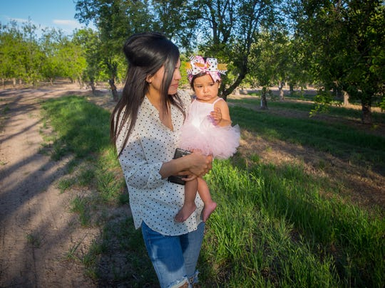 Gricelda Garcia walks with her one-year-old daughter