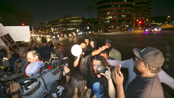 The Rev. Jarrett Maupin (center) uses a megaphone to direct protesters into the middle of 24th Street during a protest against police brutality and racial profiling at the intersection of 24th Street and Camelback Road in Phoenix on July 15, 2016. The protesters stayed in the intersection blocking traffic for a few minutes before peacefully leaving the intersection.