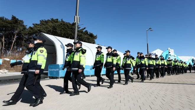 Members of the Korean police walk through Olympic Park before a hockey game.