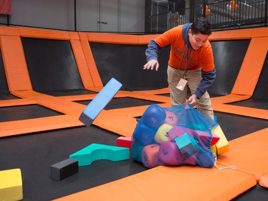 AirTime Trampoline & Game Park employee Ghazi Natsheh, 16, of Westland spreads toys across the trampolines at the indoor amusement center in Westland. AirTime is a former big box store in its second act.