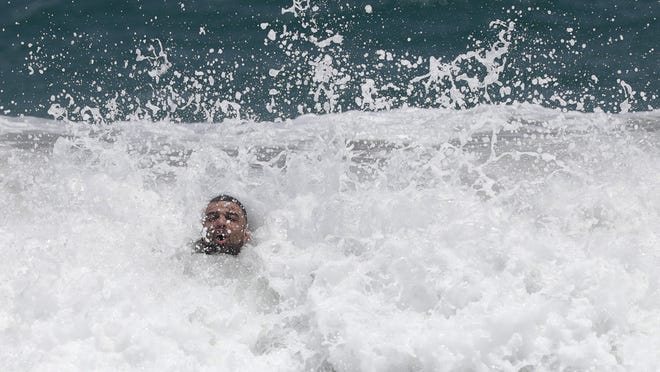 A beach goer is engulfed by a wave as he jumped in the surf on Aug. 1 in Palm Beach as Tropical Storm Isaias headed toward the Florida coast.