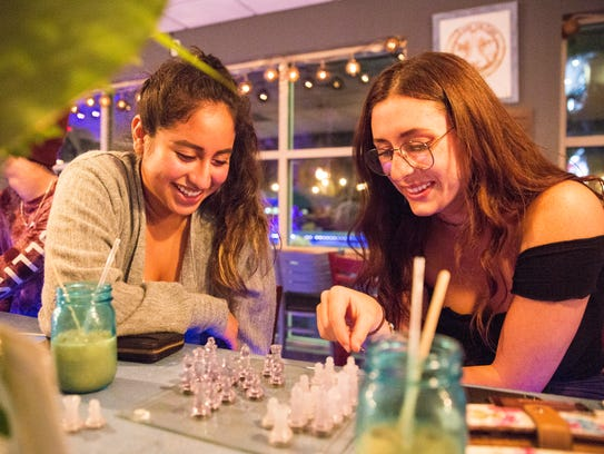 Kelly Diaz, left, and Grace Tomaielly play chess while