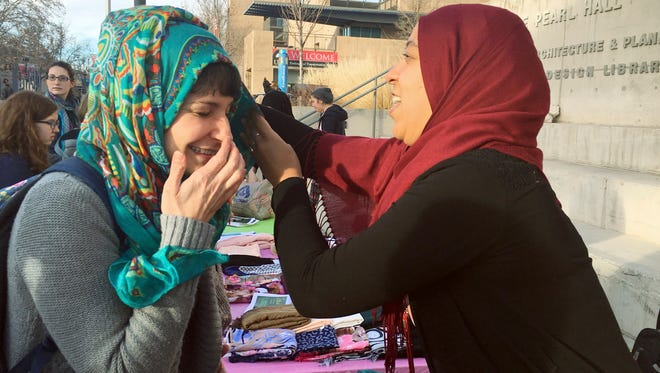 "Sarah Rivali, 33, left, tries on a hijab with the help of Aicha Nahod, of Tunsia, on the campus of the University of New Mexico in Albuquerque Wednesday, Feb. 1, 2017. Students took part in ""World Hijab Day""  an event created in 2013 in reaction to Muslim women being harassed for wearing the head covering used by some women who practice Islam."