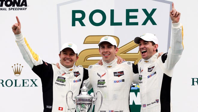 Winners of the GT LeMans Class in the IMSA 24-hour auto race, from left to right, Marcel Fassler, of Switzerland, Tommy Miner and Oliver Gavin, both of Britain, celebrate at Daytona International Speedway, Sunday, Jan. 31, 2016, in Daytona Beach, Fla.