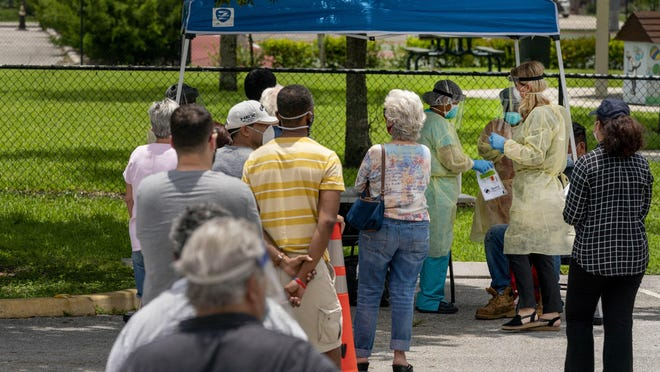 People line up to be tested for COVID-19 on June 11, 2020, in Greenacres, Florida.