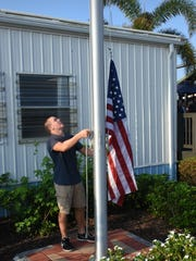 Jay Cartwright, a junior at Marco Island Academy, does the honors raising Old Glory. The island's charter high school marked its first day of classes after Hurricane Irma on Monday, Sept. 25, 2017, with a ceremony featuring a flag that had flown in war zones.