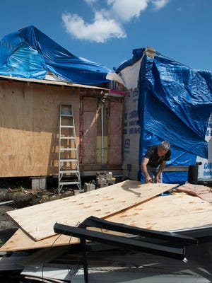 A month after a tornado ripped through town of Century, homeowner Bobby Swords continues to make repairs to his storm damaged property on Front Street.