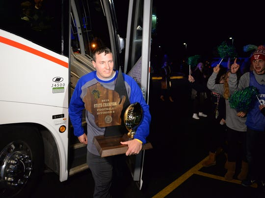 Green Bay Notre Dame assistant football coach Chris Nowak carries the championship trophy from the bus at a Nov. 20, 2015, victory rally.