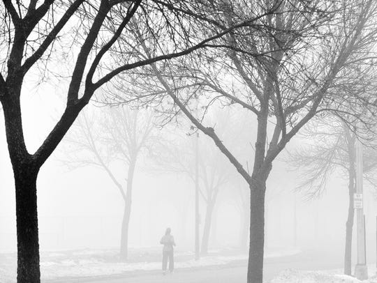 A runner gradually fades into the thick fog Dec. 14,
