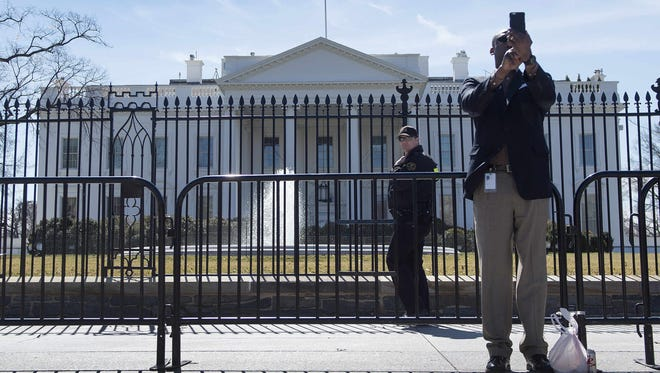 An officer with the U.S. Secret Service patrols Pennsylvania Avenue in front of the White House in Washington, DC, March 12, 2015, as a man takes a selfie.