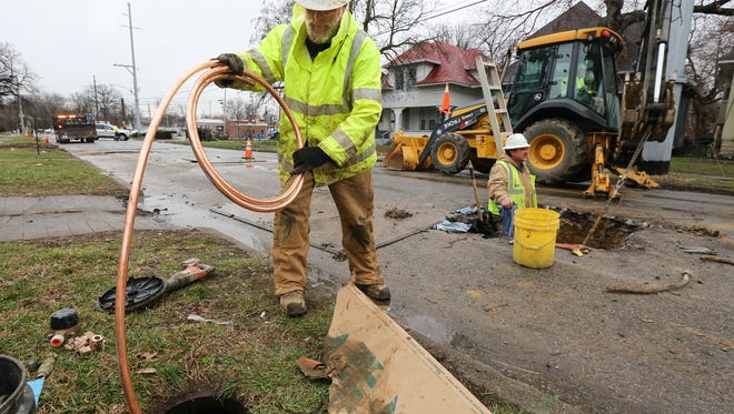 Donald Dowell, left, feeds a new copper supply main underground to Mark Mitchell, center, and Scott McHatton, who is pulling the line through using a backhoe on 34th Street in Louisville.  The copper line is being used to used to replace century-old lead lines.