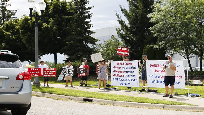 A small group of protestors are gathered outside of The Summit in Dimondale before GOP Presidential candidate Donald Trump's rally in Dimondale, Friday, Aug. 19, 2015