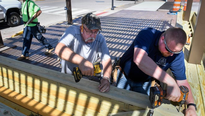 """(L-R) John Coomes, president of the Tri-County Council of Labor, and Andy Carr with Carpenters Local 224 assemble benches in the new pocket park """"The Perch"""" under construction on Second Street in Henderson Wednesday, June 6, 2018."""