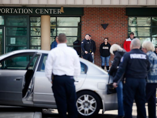 Onlookers and an Elmira police officer stand at the