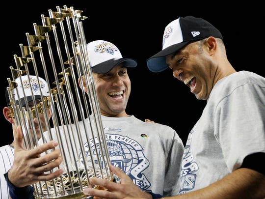 New York Yankees' Mariano Rivera, right, and Derek Jeter look at the championship trophy after winning the World Series against the Philadelphia Phillies in New York on Nov. 4, 2009.