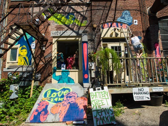 Emily Herr, on ladder, paints a mural in the alley