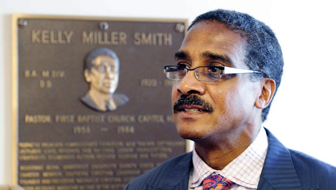 In this 2010 file photo, Dr. Kelly Miller Smith Jr. poses with a plaque honoring his father at First Baptist Church, Capitol Hill, where his father was the pastor years ago.