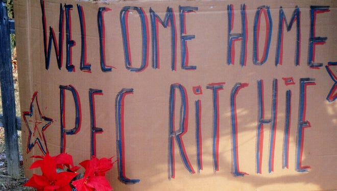 A sign in front of Ralph and Bonnie Ristenbatt's house on Smith Avenue in Lebanon welcomes home their grandson, Private First Class Austin Ritchie. Ritchie, who is based in Fort Benning, Ga., was expected to return for the holidays. When he returned to his grandparents house, an anonymous passerby placed poinsettias at the sign.