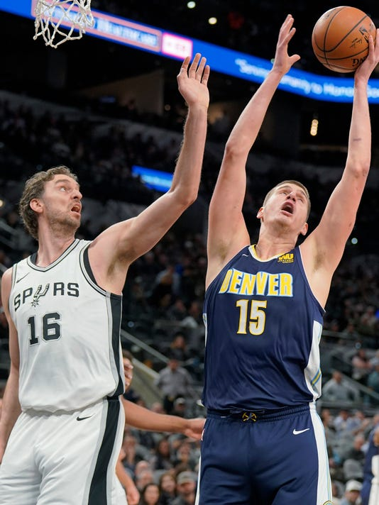 Denver Nuggets' Nikola Jokic (15) and San Antonio Spurs' Pau Gasol reach for a rebound during the first half of an NBA basketball game Tuesday, Jan. 30, 2018, in San Antonio. (AP Photo/Darren Abate)