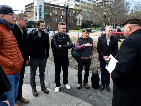 Artist Po Shu Wang, third from right, asks questions of city purchasing agent Boyce Evans, right, as the top five finalists to create art for the Cradle of Country Music Park gathered Friday.